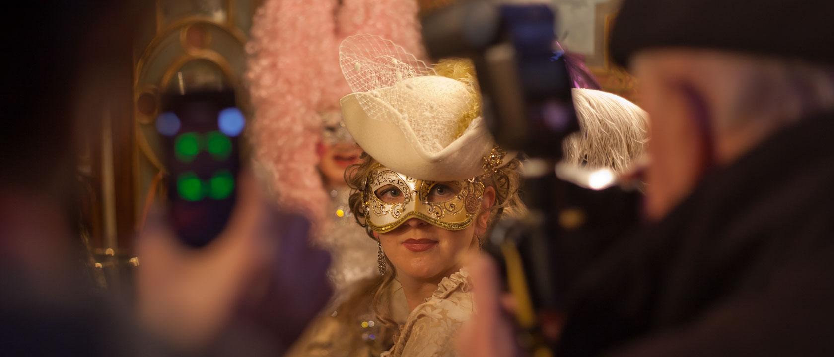 Paprazzi fotografieren eine Maske im Cafe Florian auf dem Markusplatz
